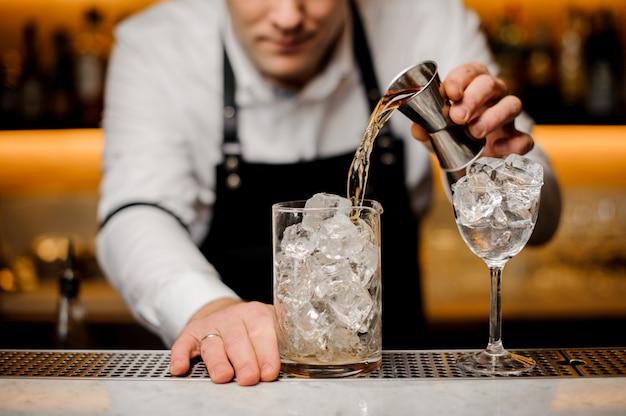 Barman, vestido com uma camisa branca, derramando bebida alcoólica em um copo com cubos de gelo Foto Premium