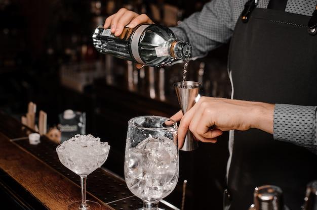 Barmans mãos derramando bebida alcoólica em uma coqueteleira para preparar um cocktail fresco Foto Premium