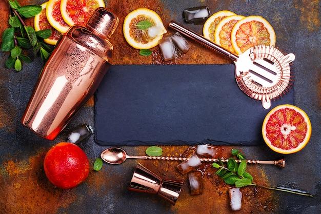 Barra de acessórios, ferramentas de bebidas e coquetel ingredientes na mesa de pedra enferrujada. Foto Premium