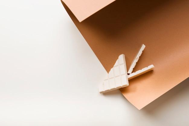Barra de chocolate branco no papel cartão marrom sobre fundo branco Foto gratuita