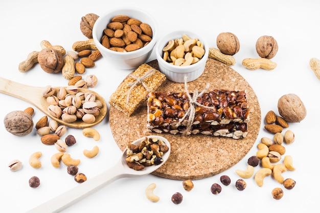 Barra de energia de frutos secos e ingredientes em fundo branco Foto gratuita