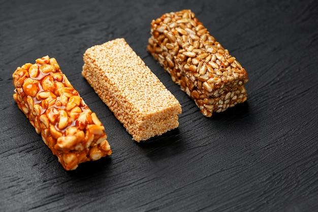 Barra de granola do cereal com sementes dos amendoins, do sésamo e de girassol em uma placa de corte em uma tabela de pedra escura. vista de cima. três barras sortidas Foto Premium