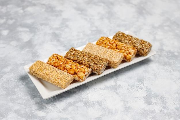 Barra de granola. lanche saudável sobremesa doce. gergelim, amendoim, girassol em mel. gozinaki é comida nacional da geórgia, doce oriental. vista superior em concreto Foto gratuita