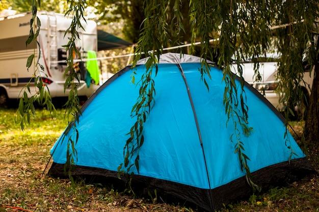 Barraca azul na sombra de uma árvore para acampar Foto gratuita