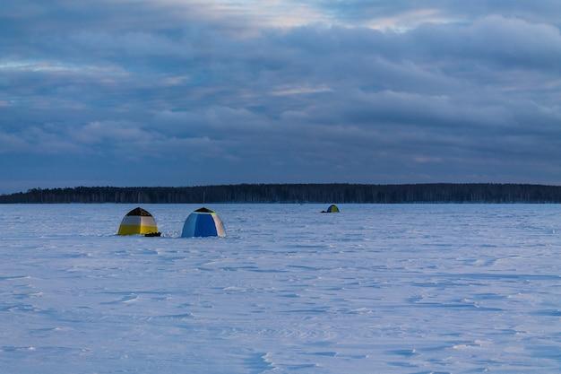 Barracas de pesca no lago congelado e coberto de neve Foto Premium
