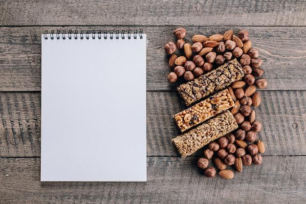 Barras da saúde, porcas misturadas e placa vazia do caderno para o texto. barras energéticas com amêndoa e avelãs Foto Premium