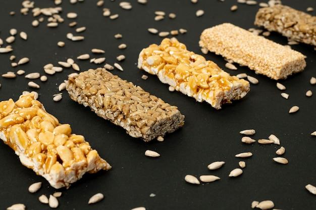 Barras de cereais close-up e sementes de girassol no fundo liso Foto gratuita