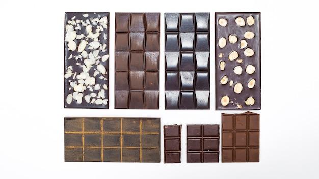 Barras de chocolate com nozes em um fundo branco. feito à mão. Foto Premium