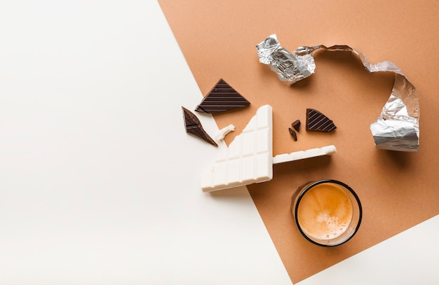 Barras de chocolate escuras e brancas quebradas com copo de café no fundo Foto gratuita