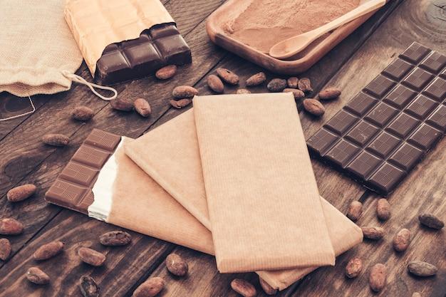 Barras de chocolate escuro com grãos de cacau na mesa de madeira Foto gratuita