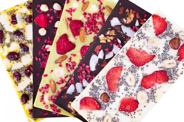 Barras de chocolate multicolorido com bagas sublimadas, nozes de coco e sementes em branco. Foto Premium