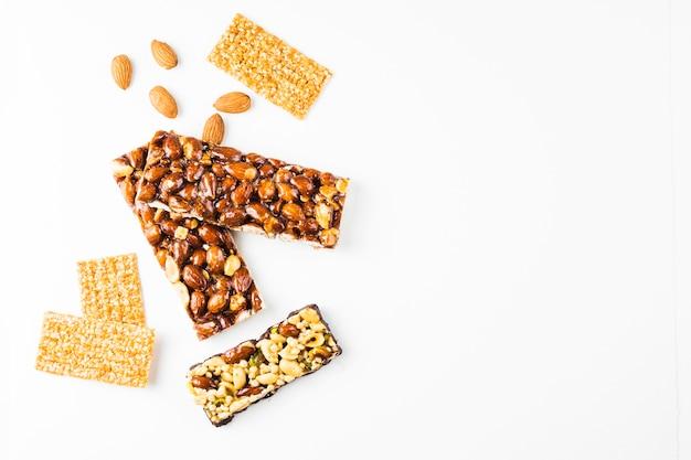 Barras de proteínas de cereais e amêndoas saudáveis contra fundo branco Foto gratuita