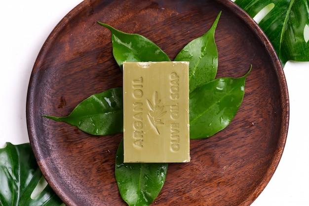 Barras de sabonetes de azeite verde natural com folhas verdes em uma placa de madeira em branco Foto Premium