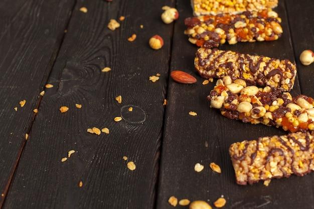 Barras saudáveis com nozes, sementes e frutas secas na mesa de madeira Foto Premium