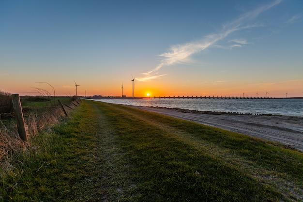 Barreira de tempestade e moinhos de vento na província de zeeland na holanda no pôr do sol Foto gratuita