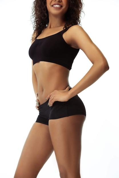 Barriga e quadris. corpo magro de mulher bronzeada isolado na parede branca. modelo feminino afro-americano com forma e pele bem cuidadas. beleza, autocuidado, perda de peso, fitness, conceito de emagrecimento. Foto gratuita