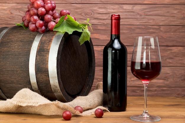 Barril de madeira com garrafa e copo de vinho Foto gratuita