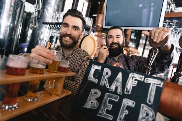 Bartenders farpados despreocupados no bar do estilo do vintage. Foto Premium