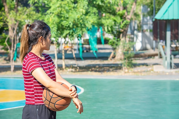 Basquetebol de couro à disposicão de uma mulher que veste uma árvore do borrão do fundo do relógio no parque. Foto Premium
