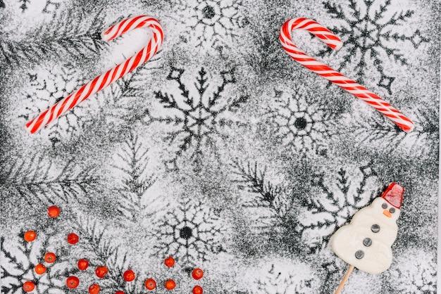 Bastões de doces e pirulito de boneco de neve em açúcar em pó Foto gratuita