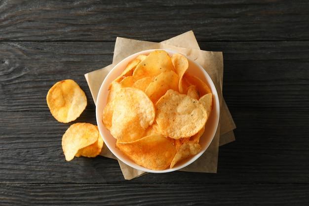 Batata frita em uma tigela, papel ofício em madeira, espaço para texto. vista do topo Foto Premium