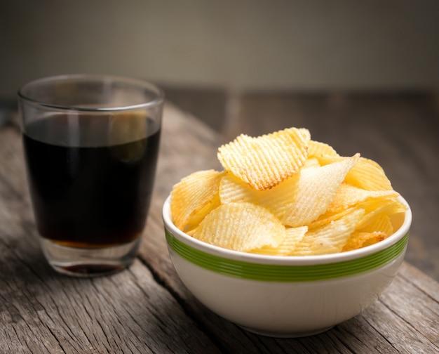 Batata frita na tigela com cola na mesa de madeira. Foto Premium