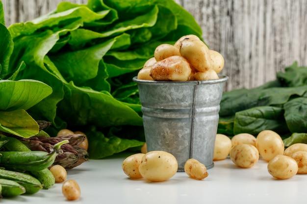 Batatas com espinafre, alface, aspargo, azeda, vagens verdes em um mini balde na parede branca e suja, vista lateral. Foto gratuita