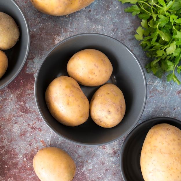 Batatas cruas em tigela cinza Foto gratuita