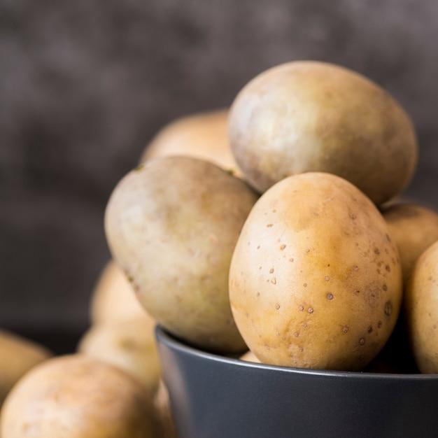 Batatas cruas em tigela close-up Foto gratuita