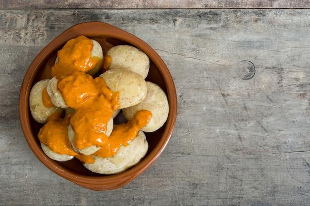 Batatas das canárias (papas arrugadas) com molho mojo na mesa de madeira Foto Premium