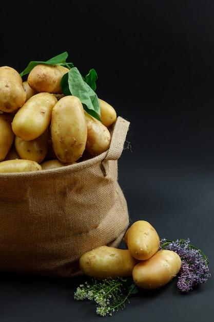 Batatas em um saco estampado com flores lilás e folhas vista lateral Foto gratuita