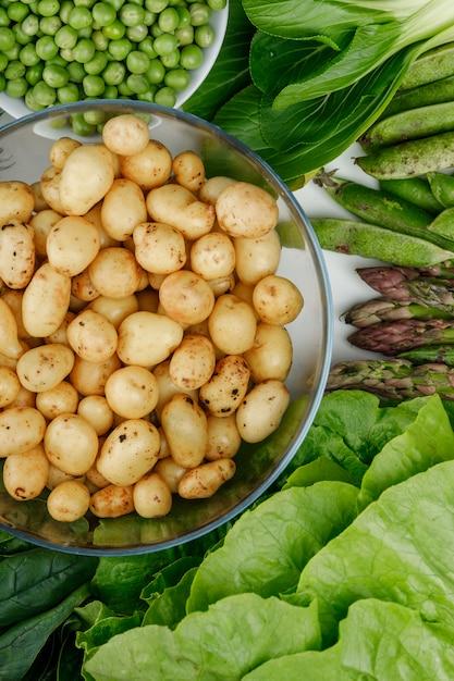 Batatas em uma tigela de vidro com vagens verdes, ervilhas, espinafre, azeda, alface, espargos vista superior em uma parede branca Foto gratuita