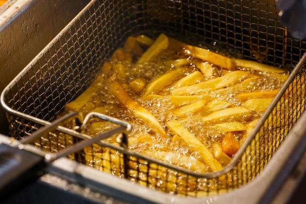 Batatas fritas batata cozinhar frito em óleo quente na cesta da máquina de fritar Foto Premium