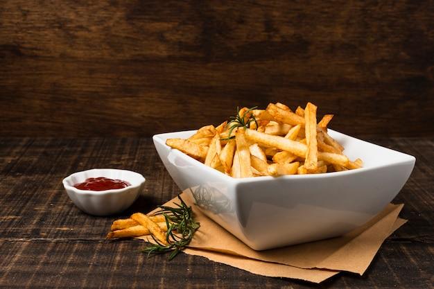 Batatas fritas com ketchup na mesa de madeira Foto gratuita