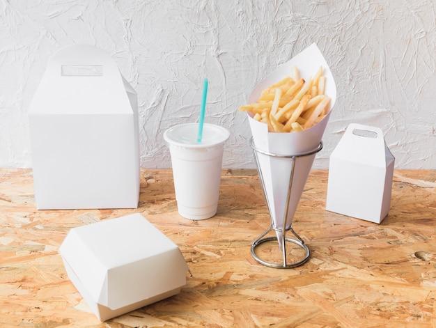 Batatas fritas; copa de eliminação e pacote de comida mock-se no fundo de textura de madeira Foto gratuita
