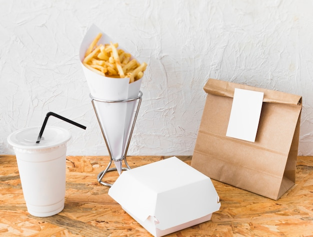 Batatas fritas; copo de eliminação; e parcela de comida na superfície de madeira Foto gratuita