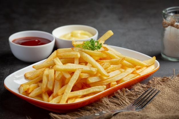 Batatas fritas crocantes com ketchup e maionese. Foto gratuita