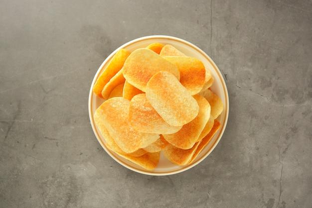 Batatas fritas crocantes isoladas sobre cinza Foto Premium