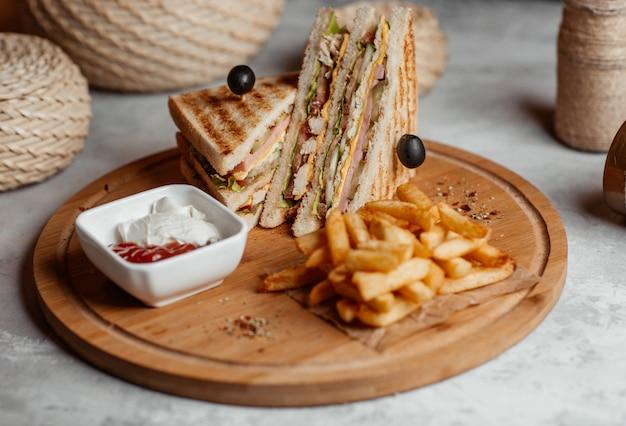 Batatas fritas crocantes, lanches, palitos e sanduíches com ketcup em uma placa de madeira Foto gratuita