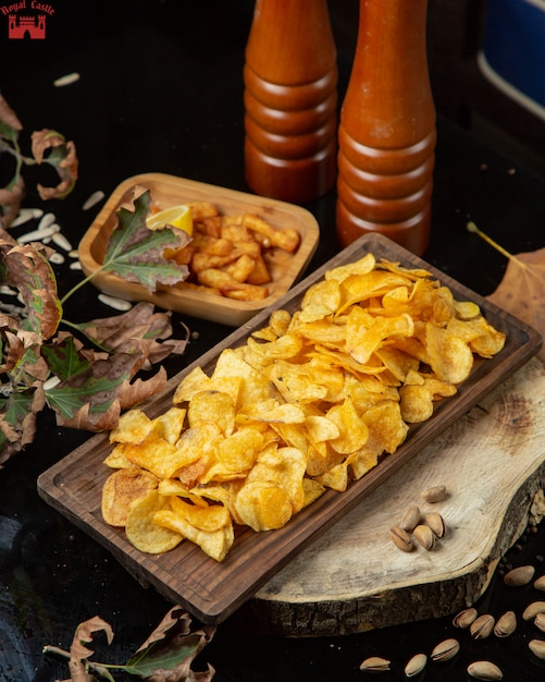 Batatas fritas e moedores de especiarias em cima da mesa Foto gratuita