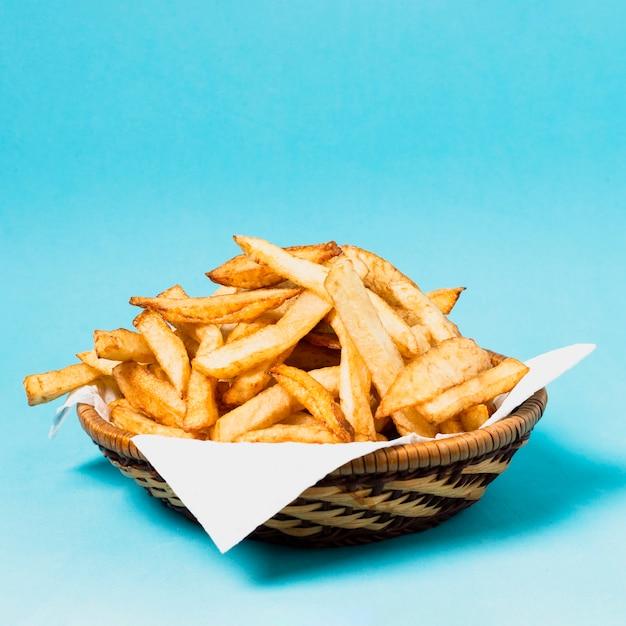 Batatas fritas em fundo azul Foto gratuita