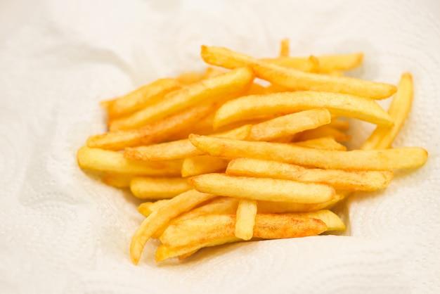 Batatas fritas em papel branco Foto Premium