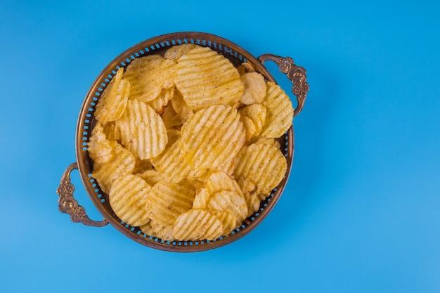 Batatas fritas em taças de prata em azul. Foto Premium