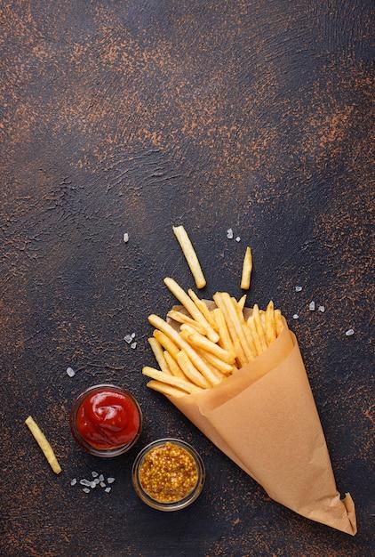 Batatas fritas em um saco de papel com molhos Foto Premium