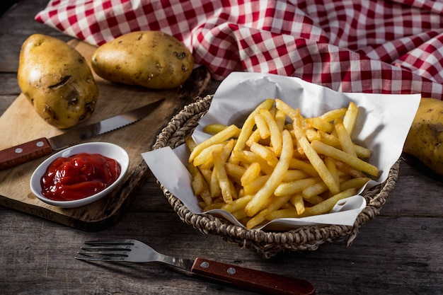 Batatas fritas na mesa de madeira Foto Premium