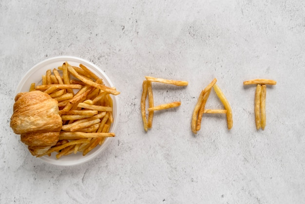 Batatas fritas; pão de croissant e gordura de enfermaria sobre superfície texturizada Foto gratuita
