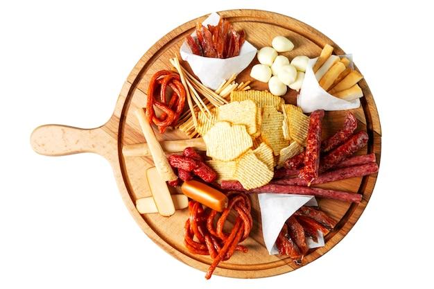 Batatas fritas, salsichas e queijos em uma placa de madeira Foto Premium