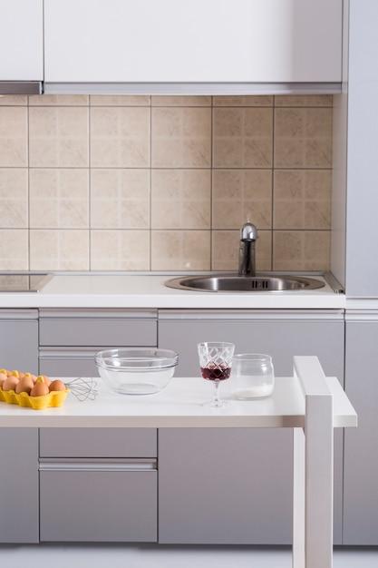 Batedor de ovos; tigela; taças de vinho e farinha na mesa na cozinha Foto gratuita