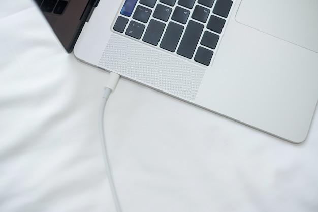Bateria de carregamento do computador portátil na cama no quarto em casa. tecnologia, carregador múltiplo de compartilhamento e conceitos de estilo de vida Foto Premium