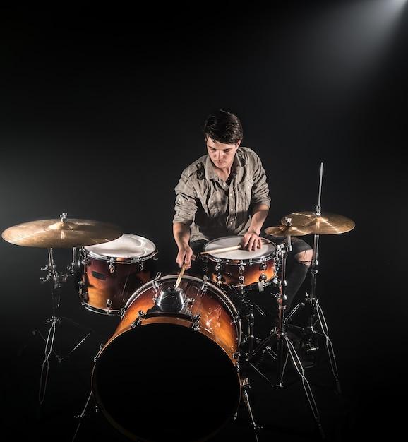 Baterista profissional tocando bateria no palco sobre o fundo preto com baquetas e look vintage. vista do topo. efeito de fumaça Foto gratuita